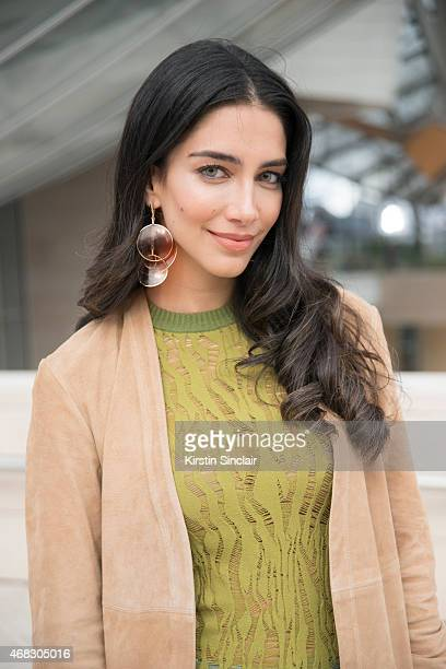 TV host and former Miss Australia Jessica Kahawaty wears a Theory coat Louis Vuitton top and earrings on day 9 of Paris Collections Women on March 11...