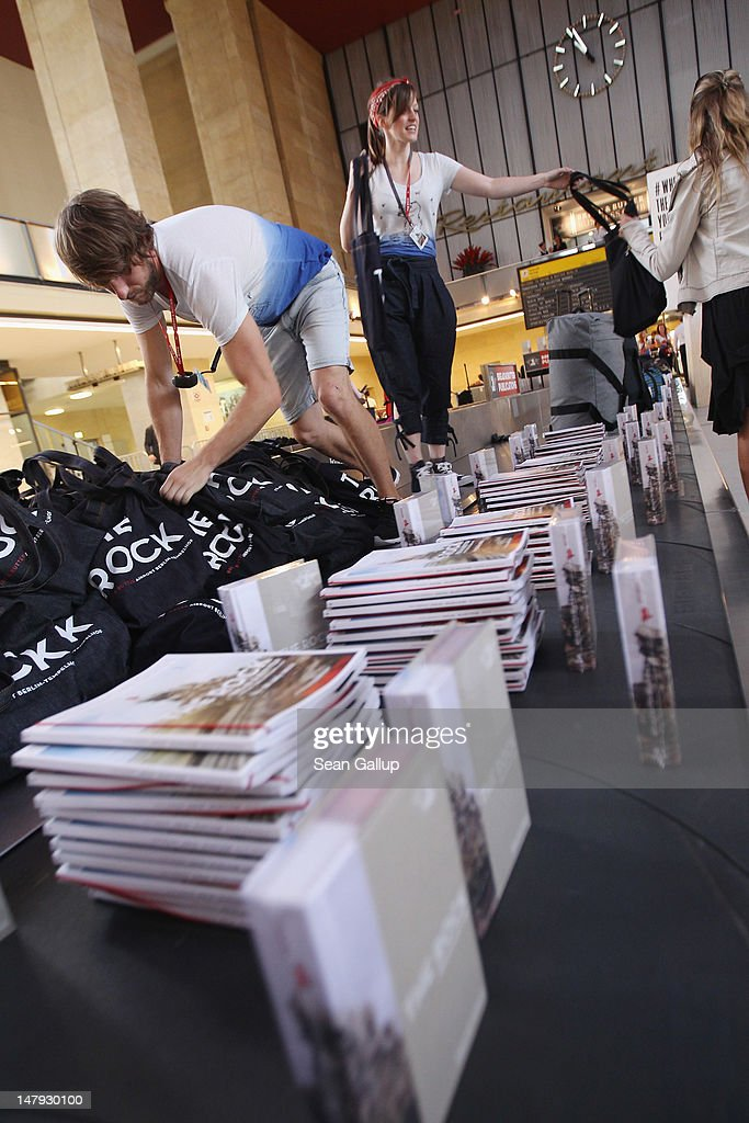 A host and hostess hand out bags and catalogues from a baggage conveyor at the 2012 Bread & Butter fashion trade fair at former Tempelhof Airport on July 6, 2012 in Berlin, Germany. Bread & Butter is the world's largest trade fair for street fashion.