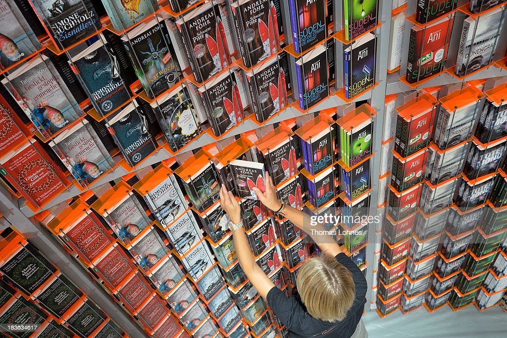 A host arranges books at the'Knaur' publishing house stand a day before the launch of the 2013 Frankfurt Book Fair on October 8, 2013 in Frankfurt, Germany. This year's fair will be open to the public from October 9-13 and the official partner nation is Brazil.