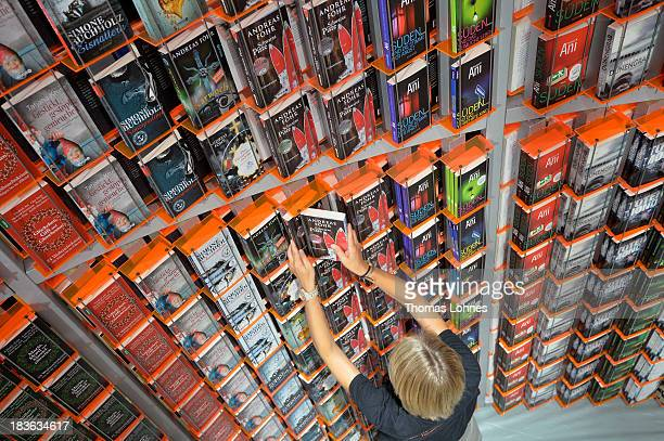 A host arranges books at the'Knaur' publishing house stand a day before the launch of the 2013 Frankfurt Book Fair on October 8 2013 in Frankfurt...