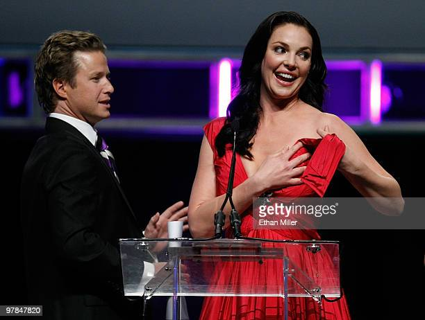 Host Billy Bush looks on as Katherine Heigl accepts the Female Star of the Year Award after part of her dress broke during the ShoWest awards...
