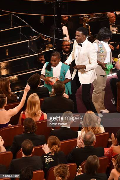 Host Chris Rock and a Girl Scout sell cookies to audience members during the 88th Annual Academy Awards at the Dolby Theatre on February 28 2016 in...