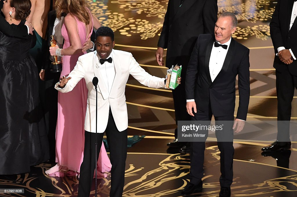 Host Chris Rock and actor Michael Keaton celebrate onstage during the 88th Annual Academy Awards at the Dolby Theatre on February 28 2016 in...