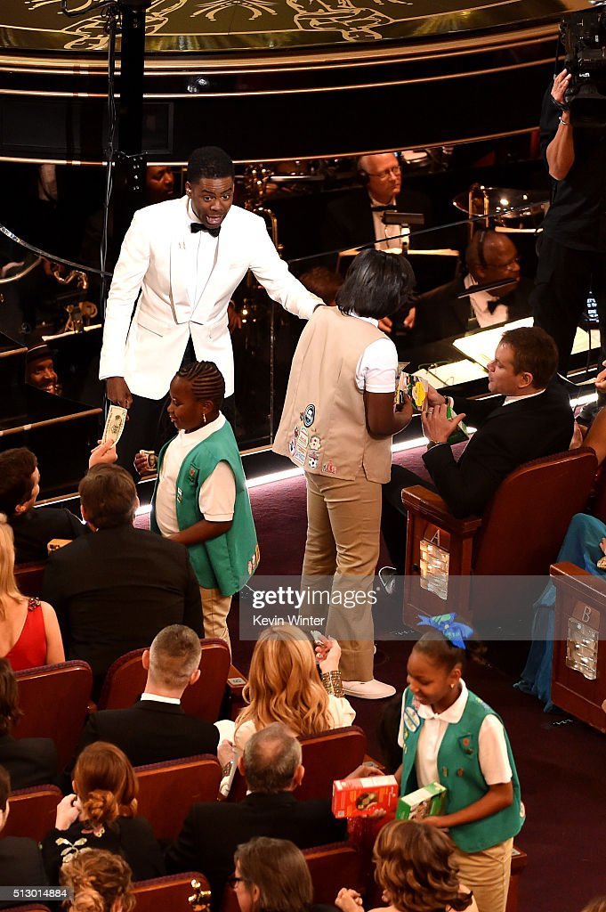 Host Chris Rock (L) and some Girl Scouts sell cookies to audience members during the 88th Annual Academy Awards at the Dolby Theatre on February 28, 2016 in Hollywood, California.