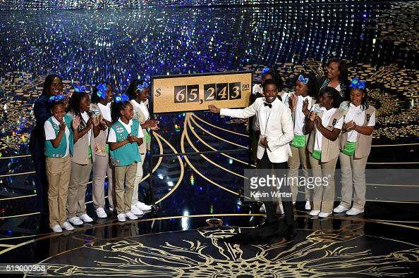 Host Chris Rock presents the amount of money collected during the show by the Girl Scouts including Rock's daughters Zahra and Lola onstage at the...
