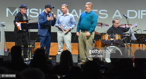 Host Cody Alan presents Robert Christie and Josh Zapor of AG Central Music the Music Makes a Difference Award during Top 100 Dealer Awards at Summer...