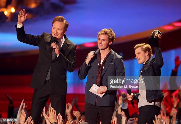 Host Conan O'Brien with actors Sam Claflin and Josh Hutcherson winners of the Movie of the Year award for 'The Hunger Games Catching Fire' speak...