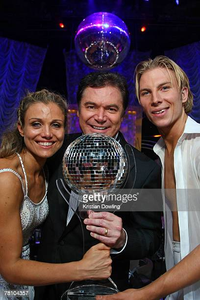 Host Darryl Sommers and final winners Bridie Carter and her partner Craig Monley pose together with their trophy following the grand final of season...