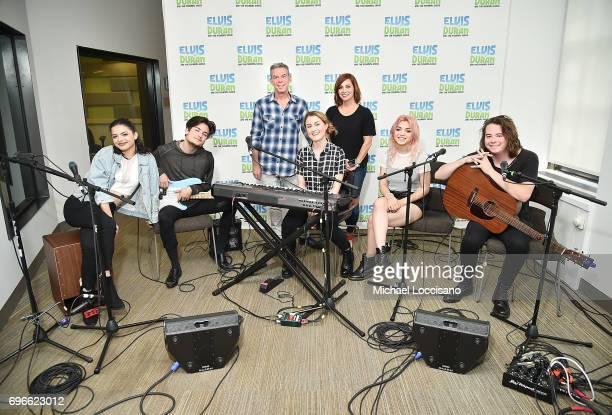 Host Elvis Duran and cohost Danielle Monaro pose with Nia Lovelis Iain Shipp Miranda Miller Rena Lovelis and Casey Moreta of Hey Violet during the...