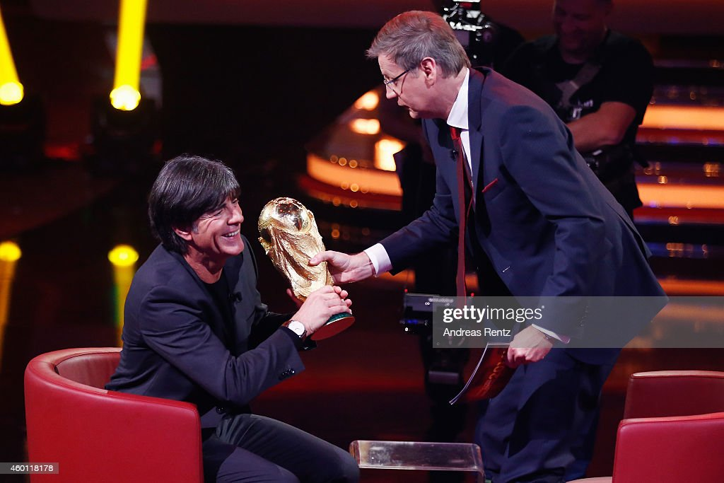 TV host Guenther Jauch (R) hands over the World Cup to Joachim Loew, Head coach of German national football team during the 2014! Menschen, Bilder, Emotionen - RTL Jahresrueckblick show on December 7, 2014 in Cologne, Germany.