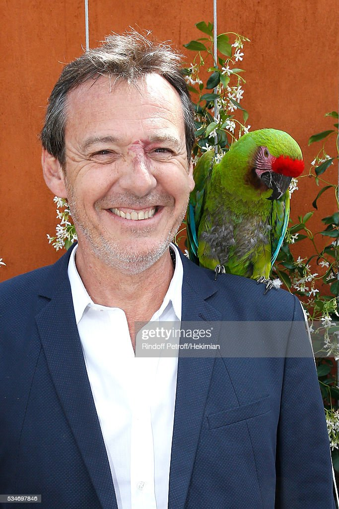 TV Host Jean-Luc Reichmann poses with parrot Zoe during the 2016 French Tennis Open - Day Six at Roland Garros on May 27, 2016 in Paris, France.