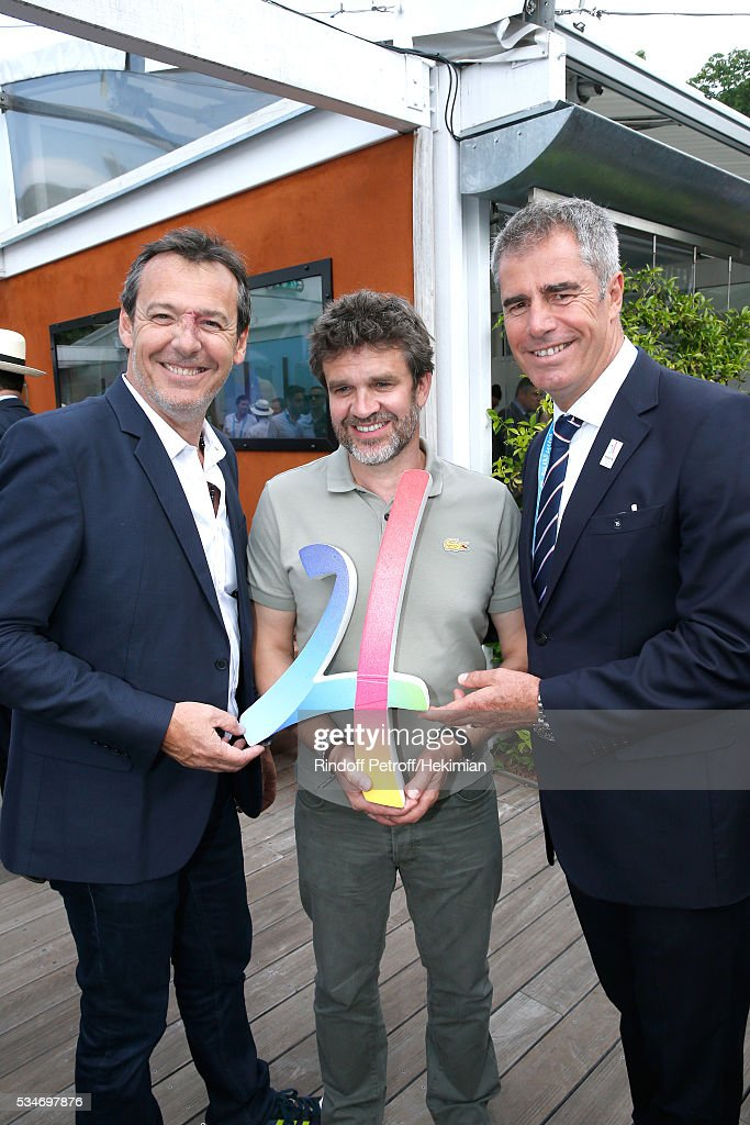 TV Host Jean-Luc Reichmann, sports journalist Herve Mathoux and animator Marc Maury pose with the Logo of the Paris 2024 Olympic Games Candidature during the 2016 French Tennis Open - Day Six at Roland Garros on May 27, 2016 in Paris, France.