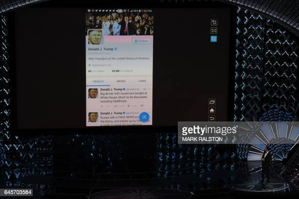 Host Jimmy Kimmel checks US President Donald Trump's twitter account on a giant screen at the 89th Oscars on February 26 2017 in Hollywood California...