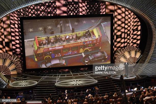 Host Jimmy Kimmel performs on stage in front of a screen showing a tour bus at the 89th Oscars on February 26 2017 in Hollywood California / AFP /...