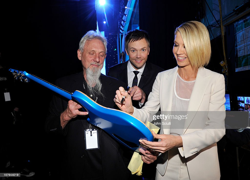 Host Joel McHale (C) and actress Jenna Elfman (R) signs the Chase Freedom blue guitar, won by a lucky winner at the American Giving Awards presented by Chase held at the Pasadena Civic Auditorium on December 7, 2012 in Pasadena, California.
