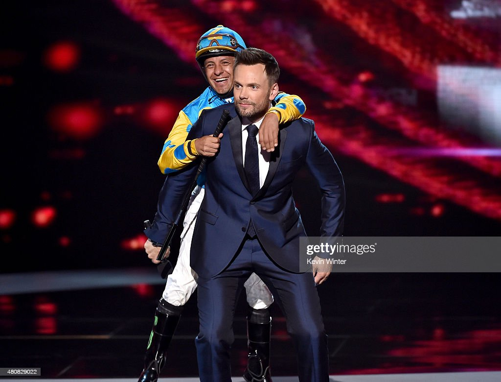 Host Joel McHale and jockey Victor Espinoza walk onstage during The 2015 ESPYS at Microsoft Theater on July 15 2015 in Los Angeles California