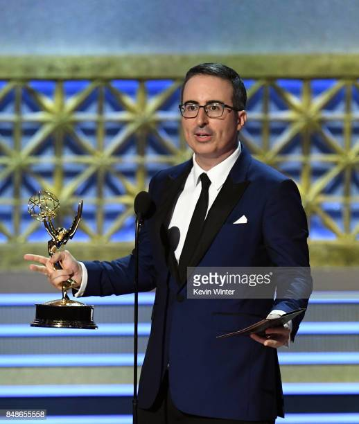 Host John Oliver accepts the Outstanding Writing for a Variety Series for 'Last Week Tonight with John Oliver' onstage during the 69th Annual...