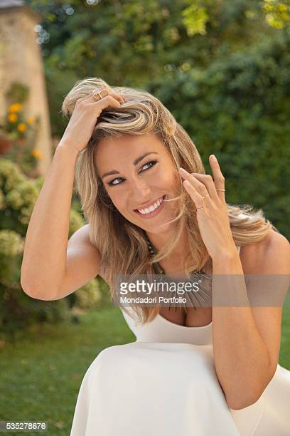 TV host Mia Ceran of TV show Uno mattina Estate squatting with a smile for a photoshooting Rome 5th August 2015