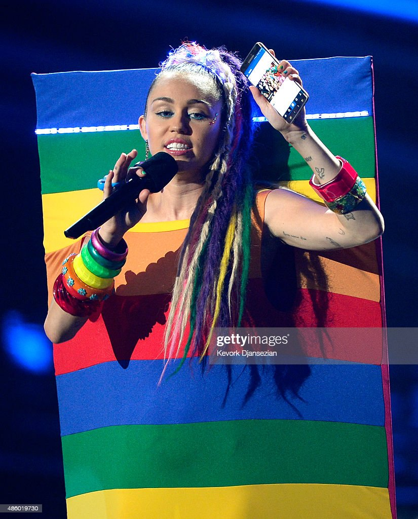 Host Miley Cyrus, styled by Simone Harouche, holding a Samsung phone speaks onstage during the 2015 MTV Video Music Awards at Microsoft Theater on August 30, 2015 in Los Angeles, California.
