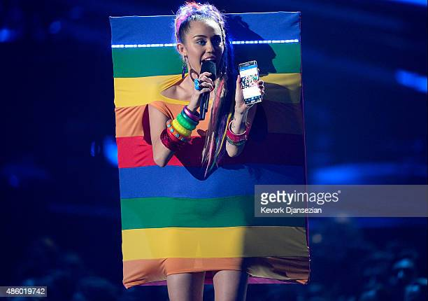 Host Miley Cyrus styled by Simone Harouche holding a Samsung phone speaks onstage during the 2015 MTV Video Music Awards at Microsoft Theater on...