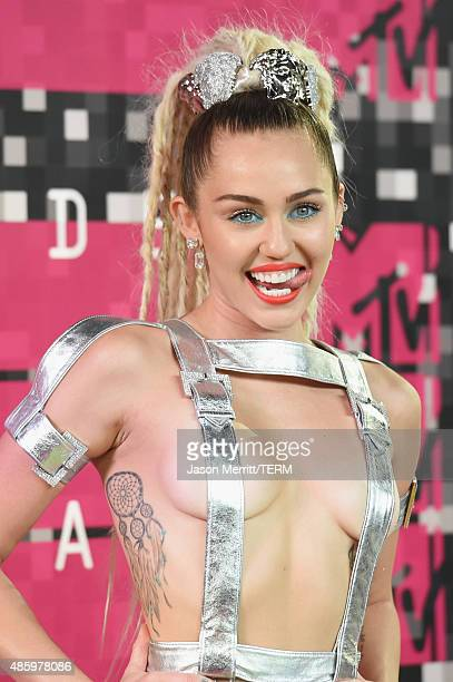 Host Miley Cyrus styled by Simone Harouche wearing a custom Versace outfit and boots attends the 2015 MTV Video Music Awards at Microsoft Theater on...