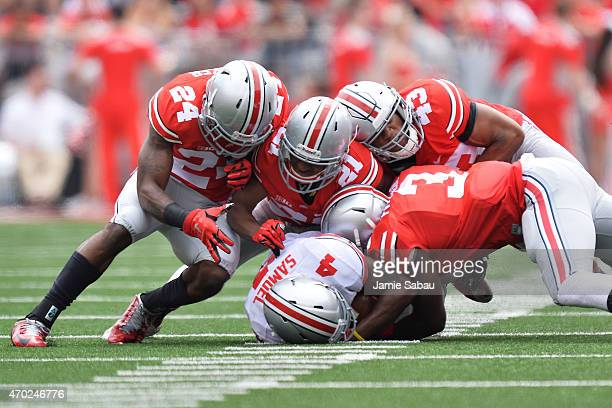 A host of Ohio State Buckeyes from the Scarlet team gang tackle Curtis Samuel of the Ohio State Buckeyes Gray team in the first half during the...