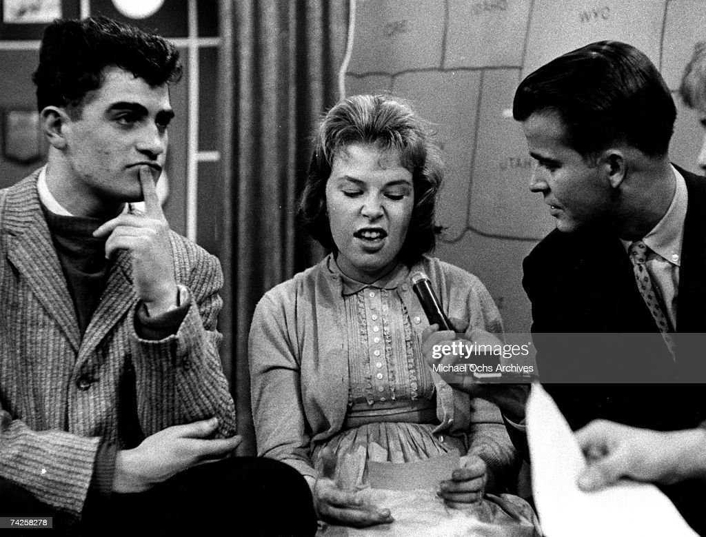 Host of the television show 'American Bandstand' Dick Clark gets candid reactions from a snarling female and pensive male teenagers during the...