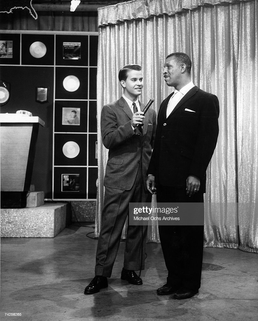 Host of the television show 'American Bandstand' Dick Clark interviews a singer in circa 1957