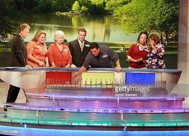 Host Pat Sajak helps Tara Carroll Paula Deen James Thompson actor Steve Schirripa Joy Bryant and actress Sherri Shepherd spin the wheel during a...