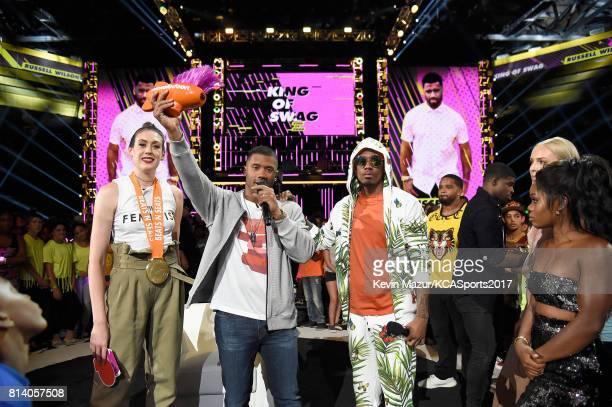 Host Russell Wilson accepts the King of Swag award from WNBA player Breanna Stewart TV personality Nick Cannon MLB player Prince Fielder NHL player P...