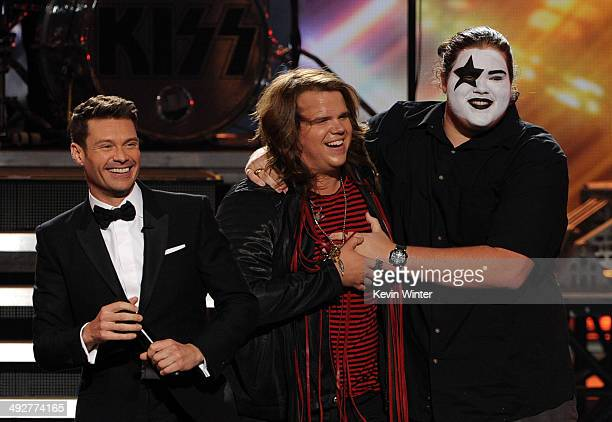Host Ryan Seacrest American Idol Finalist Caleb Johnson and his brother Houston Johnson onstage during Fox's 'American Idol' XIII Finale at Nokia...