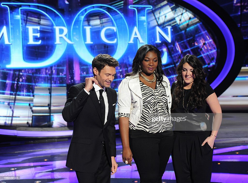 Host Ryan Seacrest (L) and top 2 contestants Candice Glover (C) and Kree Harrison during the coin toss to see who performs first on finale night onstage at FOX's 'American Idol' Season 12 Top 3 to 2 Live Elimination Show on May 9, 2013 in Hollywood, California.