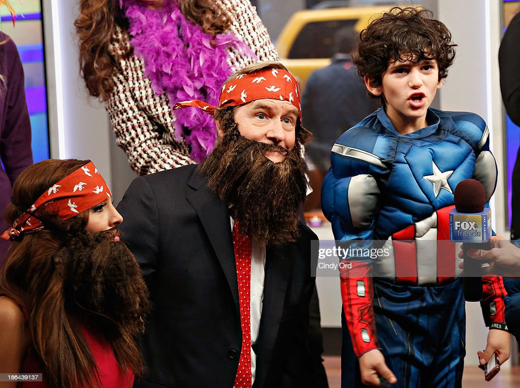 Host Steve Doocy (C) wears a 'Duck Dynasty' costume as 'FOX & Friends' celebrates Halloween at FOX Studios on October 31, 2013 in New York City.