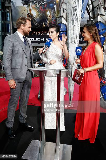 Host Steven Gaetjen Actress Li Bingbing and Host Oezlem Evans attend the european premiere of 'Transformers Age of Extinction' at Sony Centre on June...
