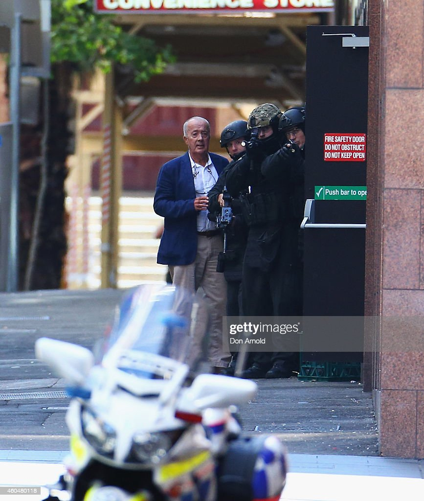 A hostage is seen outside the Lindt Cafe Martin Place on December 15 2014 in Sydney Australia Police attend a hostage situation at Lindt Cafe in...