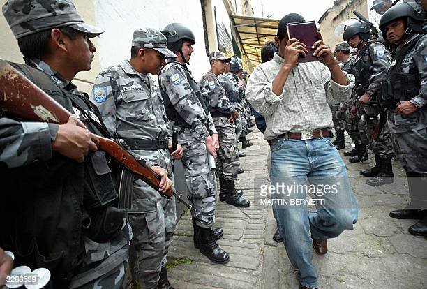 A hostage leaves guarded by the Police Prison II in Quito as mutineers released him 08 April 2004 Ecuador's interior minister Raul Baca said Thursday...