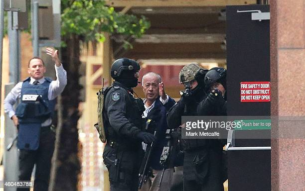 A hostage runs to safety outside the Lindt Cafe Martin Place on December 15 2014 in Sydney Australia Police attend a hostage situation at Lindt Cafe...