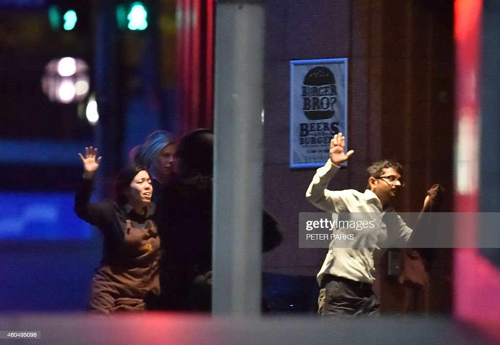 Hostages run out of a cafe in the central business district of Sydney on December 16 2014 Police stormed the Sydney cafe where a gunman had taken...