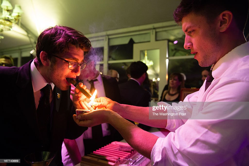 MSNBC hosted this after party following the White House Correspondents Dinner. Ben Droz, left, has his cigar lit by Lewis Nelson, of Cigar Row.