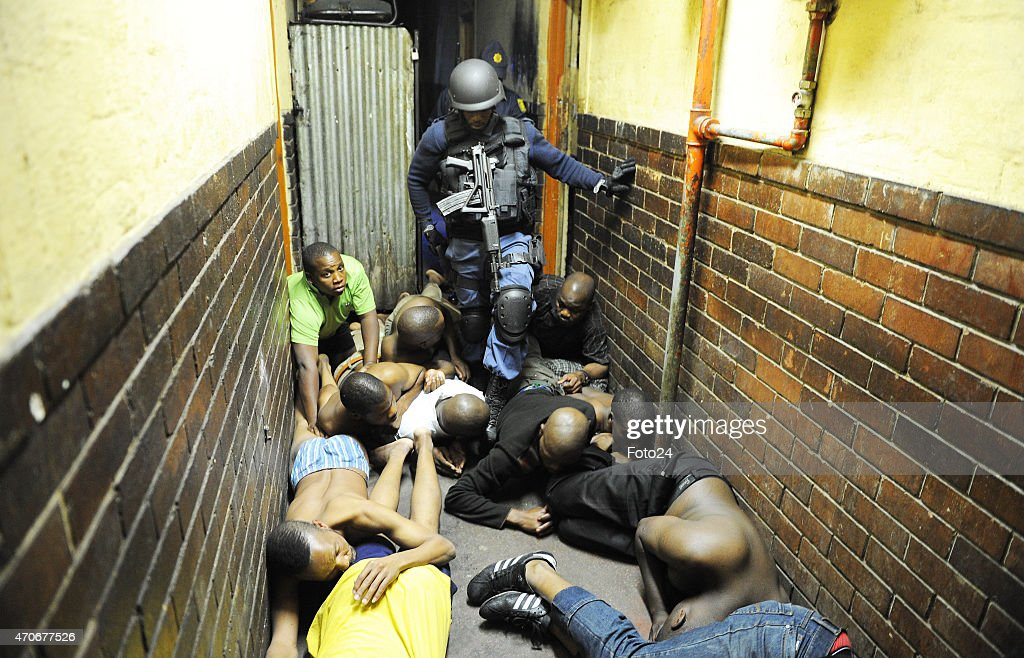 Hostel dwellers lie on the floor during a raid by police at the Jeppestown Hostel on April 21 2015 in Johannesburg South Africa After xenophobic...
