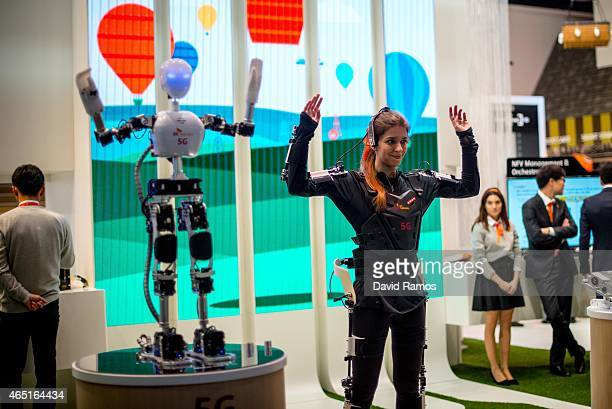 A hostes performs with robot under control by 5G Technology at SK Telekom pavilion during the second day of the Mobile World Congress 2015 at the...
