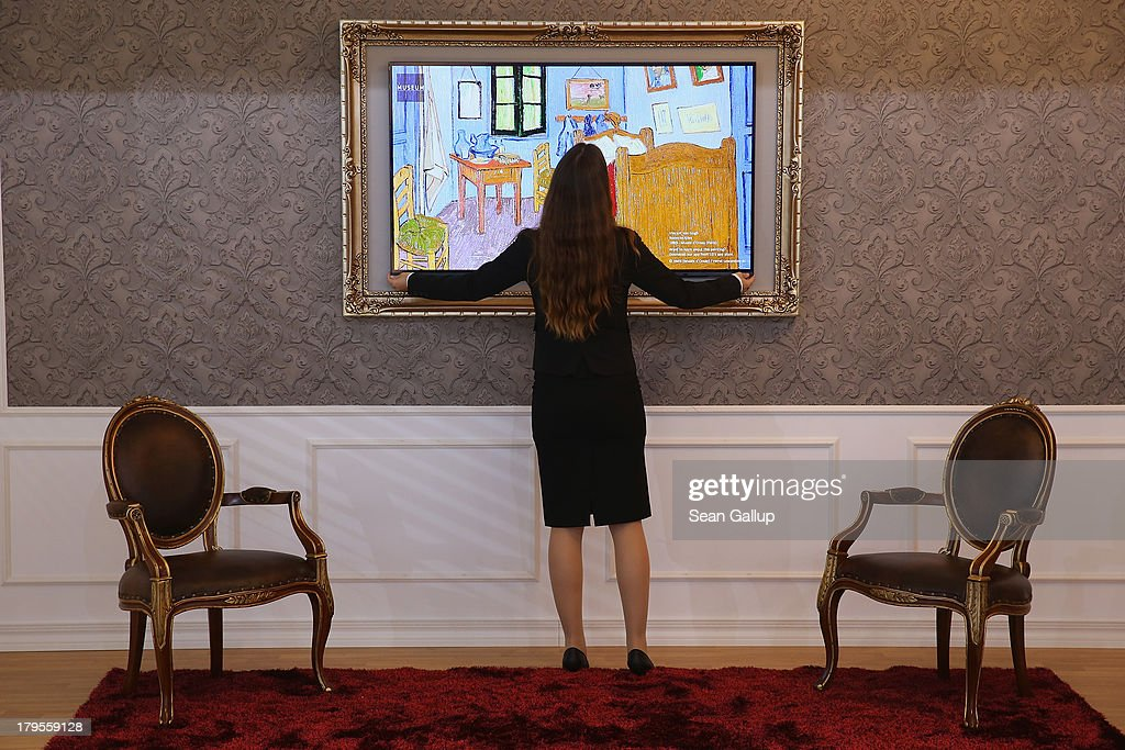 A hostess adjusts an HD television that is framed as a reproduction of Vincent van Gogh's 'Room in Arles' at the LG stand at the IFA 2013 consumer electronics trade fair on September 5, 2013 in Berlin, Germany. The 2013 IFA will be open to the public from September 6-11.