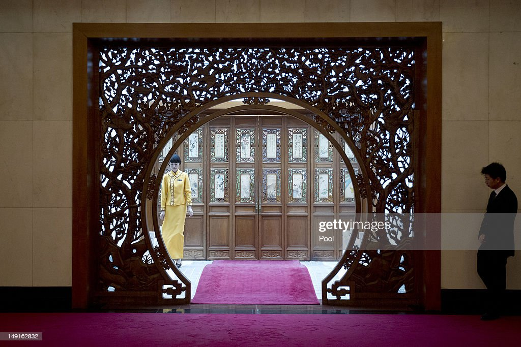 A hostess (L) and an unidentified official, stand outside closed doors of a room where Chinese State Councilor Dai Bingguo is waiting to greet visiting U.S. National Security Advisor Tom Donilon at the Diaoyutai State Guesthouse on July 24, 2012 in Beijing, China. The two are expected to discuss a range of international issues, including Syria, Iran and N. Korea.