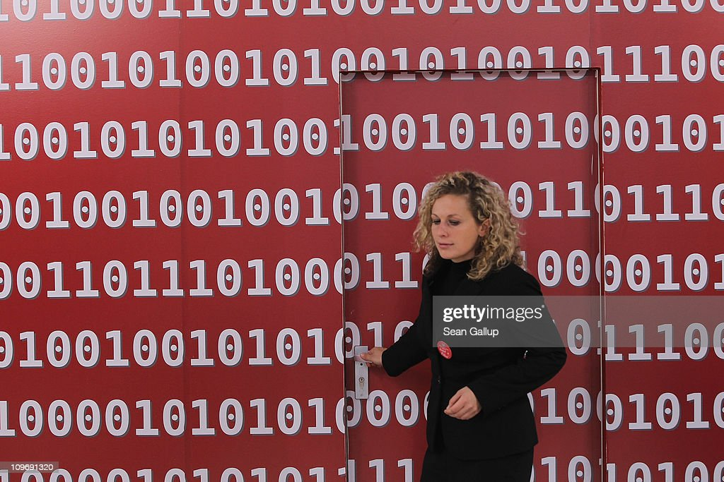 A hostess, at the photographer's request, emerges from a room covered in zeros and ones at the stand of the Polish Ministry of Economy at the CeBIT technology trade fair on March 1, 2011 in Hanover, Germany. CeBIT 2011 will be open to the public from March 1-5.