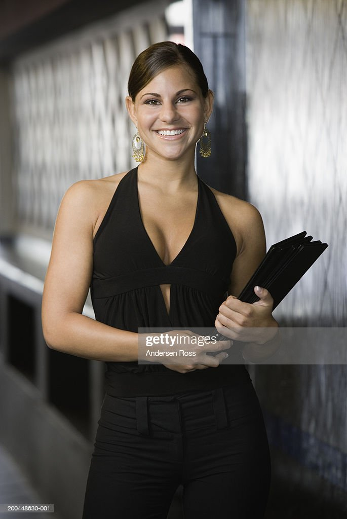 Hostess carrying menus in restaurant, smiling, portrait : Stock Photo