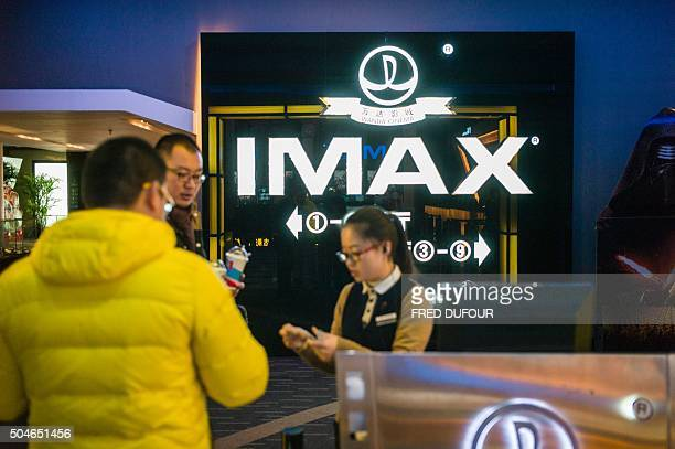 A hostess checks tickets at the Wanda cinema next to the Wanda Group building in Beijing on January 12 2016 Chinese conglomerate Wanda Group is...