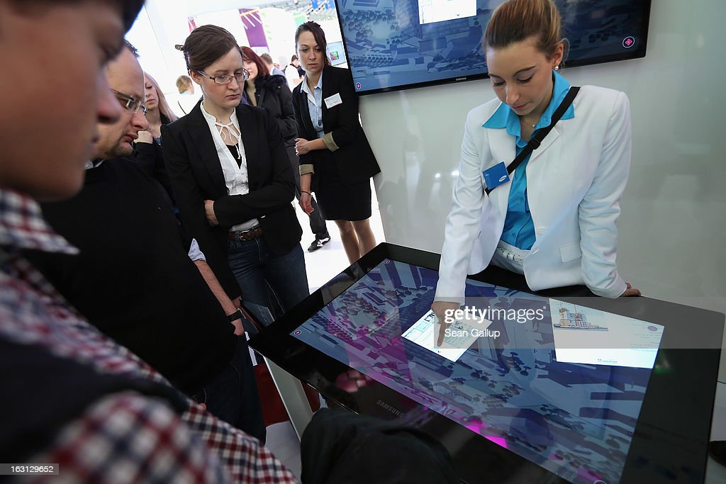 A hostess demonstrates a SUR40 touch display at the Samsung stand at the 2013 CeBIT technology trade fair on March 5, 2013 in Hanover, Germany. CeBIT will be open March 5-9.