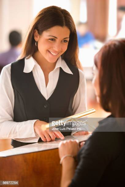 Hostess helping customer at restaurant