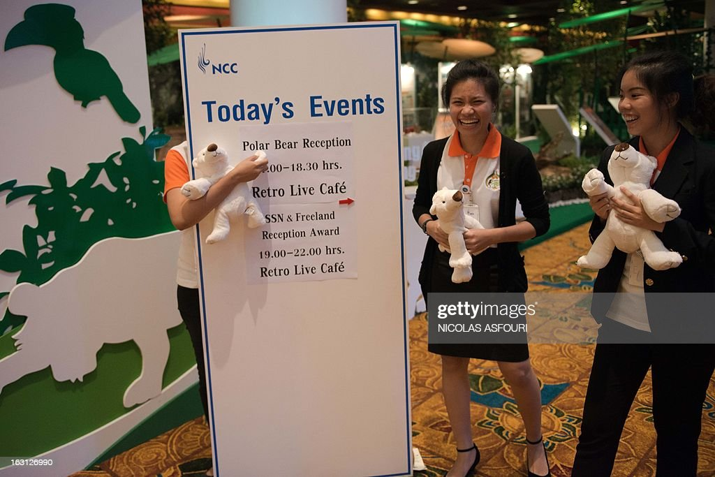 A hostess (L) hides behind an information board as she holds a teddy bear to indicate where a cocktail and photo exhibition is held by Russia and international NGO's at the Convention on International Trade in Endangered Species (CITES) in Bangkok on March 5, 2013. Global conservationists converged on Bangkok on March 3 for the start of endangered species talks, as host Thailand was forced onto the defensive over the rampant smuggling of ivory through its territory. AFP PHOTO/ Nicolas ASFOURI