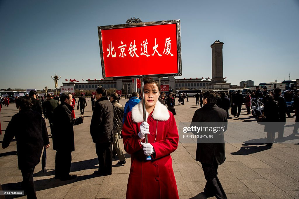 TOPSHOT A hostess holds a hotel information board for delegates at the third plenary meeting of the Chinese People's Political Consultative...